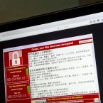 FILE - In this May 13, 2017 file photo, a screenshot of the warning screen from a purported ransomware attack, as captured by a computer user in Taiwan, is seen on laptop in Beijing.  Global cyber chaos is spreading Monday, May 14,  as companies boot up computers at work following the weekend's worldwide ransomware cyberattack. The extortion scheme has created chaos in 150 countries and could wreak even greater havoc as more malicious variations appear. The initial attack, known as WannaCry, paralyzed computers running Britain's hospital network, Germany's national railway and scores of other companies and government agencies around the world.  (AP Photo/Mark Schiefelbein, File)