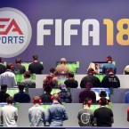 Visitors play the latest FIFA 18 soccer game from EA Sports at the Gamescom fair for computer games in Cologne, Germany, Tuesday, Aug. 22, 2017. The leading European trade fair for digital gaming culture is the meeting point for global companies from the entertainment industry and the international gaming community. (AP Photo/Martin Meissner)
